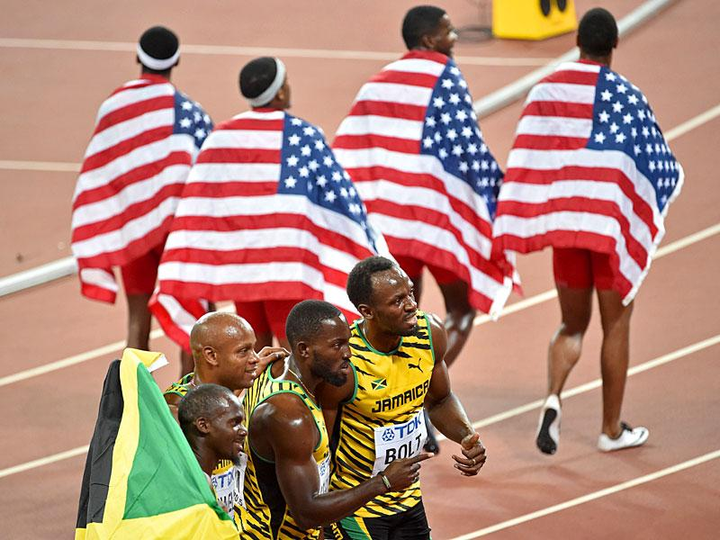 USA's relay team members Tyson Gay, Mike Rodgers, Trayvon Bromell and Justin Gatlin (top) walk with national flags past Jamaica's winning team (L-R) Carter, Powell, Ashmeade and Bolt at the end of the final of the men's 4x100 metres relay. (AFP Photo)