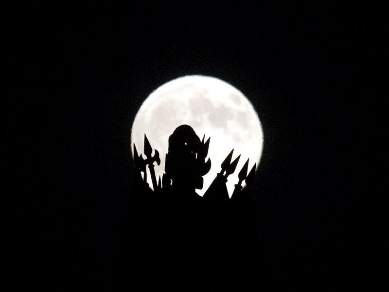 A statue on the roof of the Portuguese finance ministry in Lisbon is silhouetted against 'supermoon' full moon.(AP Photo)