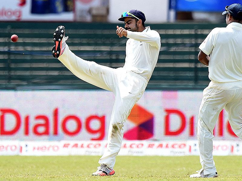 Indian Test captain Virat Kohli, left, kicks the ball in celebration after taking a catch to dismiss Perera. (AFP Photo)