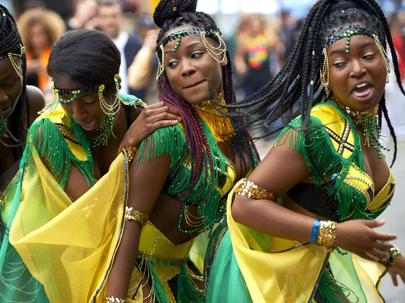 Performers dance on the first day of the Notting Hill Carnival in London on August 30, 2015. (AFP)