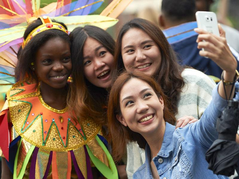 A group of women take a selfie with a performer on the first day of the Notting Hill Carnival in London on August 30, 2015. (AFP)
