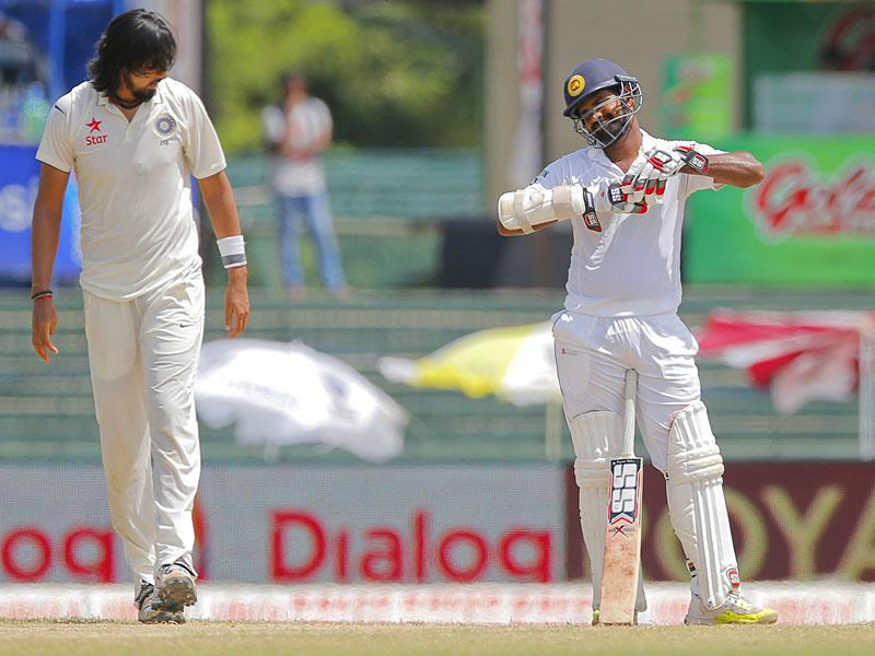Sharma, left, walks back toward his run-up after bowling to Thirimanne. (AP Photo)