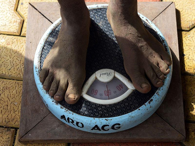 A youth stands on a weighing scale while being measured at an army recruitment rally (AFP Photo)