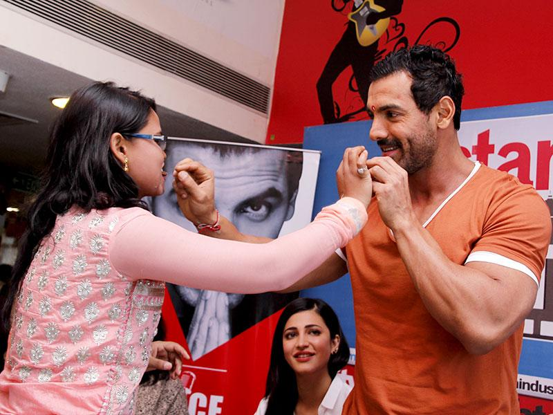 Sweet memories! A fan offers sweets to John Abraham after tying rakhi on his wrists. (Photo: Shivam Saxena/HT)
