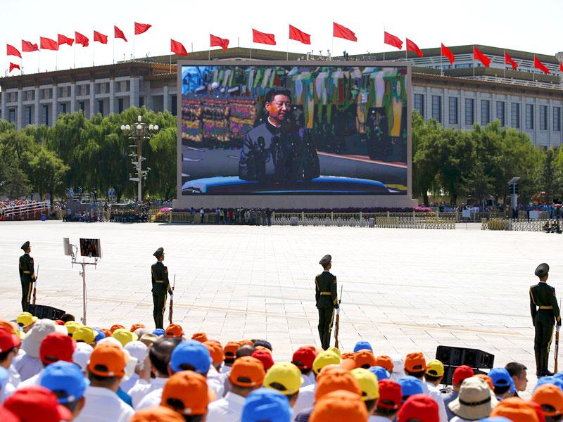 A screen displays Chinese President Xi Jinping reviewing the army at the Tiananmen Square, at the beginning of the military parade. (Reuters Photo)