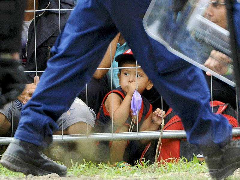 A boy sits behind a fence as a police officer walks past at the migrant reception centre in Roszke, Hungary, on September 4, 2015. (Reuters Photo)