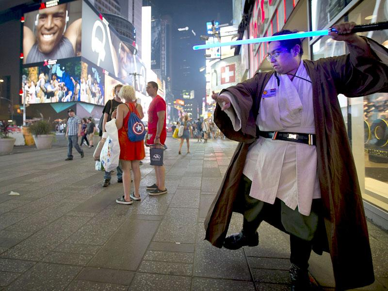 A fan brandishes his newly purchased lightsaber at Times Square, New York. (Reuters)