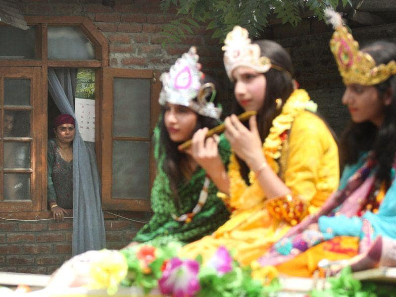 A Muslim woman looks out of a window as pandit children dressed up as Lord Krishna take part in a rally on the occasion of Janmashtami in Kashmir's capital Srinagar on Saturday. (Abid Bhat/ HT Photo)