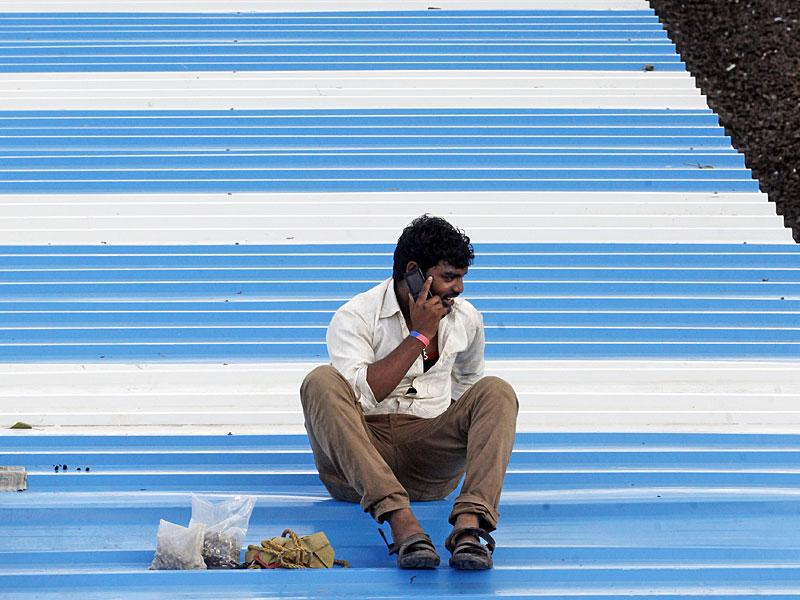 A railway worker sits on the roof of a platform and talks on the phone while carrying out maintenance work, at Mumbai Central. (Pratham Gokhale/HT photo)