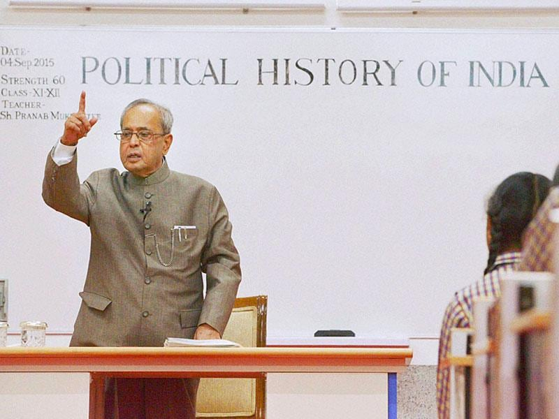 President Pranab Mukherjee teaching students at a government school on Teacher's Day eve in New Delhi on Friday. (PTI photo)