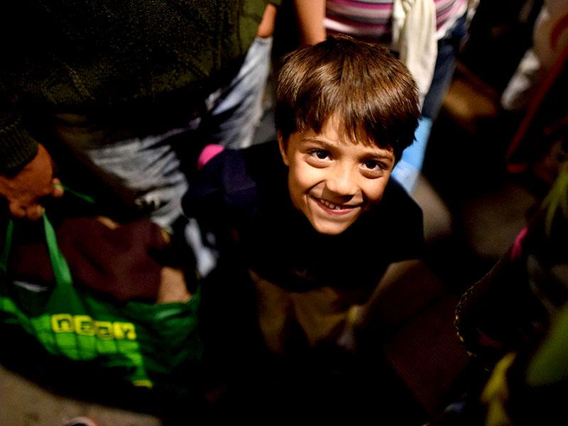 A migrant boy smiles between others at the railway station in Saalfeld, eastern Germany, after their arrival in a special train from Austria. (AFP Photo)