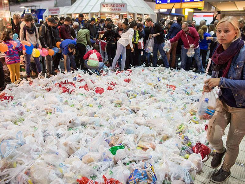 People surround hundreds of bags containing food as they wait for the arrival of a special train from Austria transporting hundreds of migrants at the main train station in Frankfurt am Main, western Germany. Germany expected up to 7,000 migrants who have been stuck in Hungary to cross into the country via Austria on Saturday. (AFP Photo)