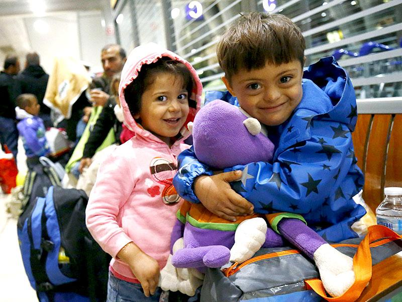 Two Syrian children laugh as they cuddle a stuffed toy given by well-wishers after they arrived in a train from Budapest's Keleti station at the airport in Frankfurt, Germany. Thousands of migrants were bussed to the Hungarian border by a right-wing government that had tried to stop them but was overwhelmed by the sheer numbers reaching Europe's frontiers. (Reuters Photo)