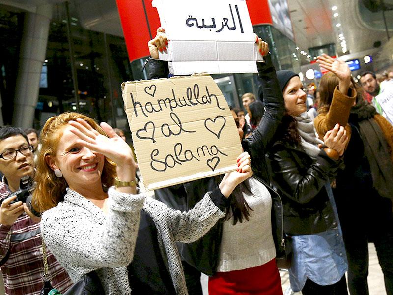 Well-wishers applaud and hold up signs welcoming migrants as Syrian families disembark a train that departed from Budapest's Keleti station to the airport in Frankfurt, Germany. The asylum seekers met with unexpected hospitality with boxes of supplies, and even candies and toys for children. (Reuters Photo)