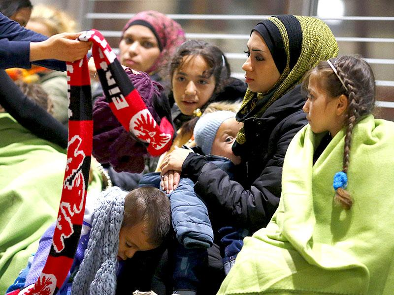 Well-wishers offer warm clothing to Syrians after they arrived on a train from Budapest to Frankfurt. More than 7,000 migrants were taken in by Germany and Austria after the immigration-aversive Hungarian government denied asylum without proper documentation, blocking them in the Keleti train station for several days. (Reuters Photo)