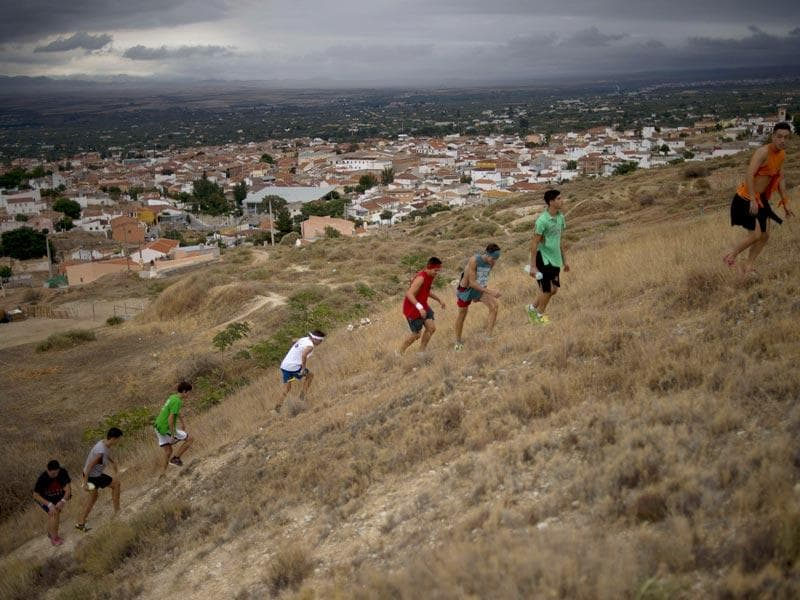 People climb a hill as they celebrate Cascamorras in Baza. (AFP Photo)