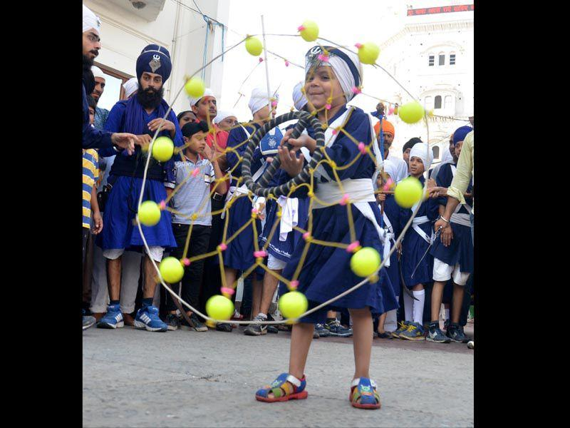 A kid performing 'gatka' during a 'nagar kirtan' to mark the 411th anniversary of installation of Guru Granth Sahib, outside the Golden Temple in Amritsar on Monday. (Sameer Sehgal/HT)