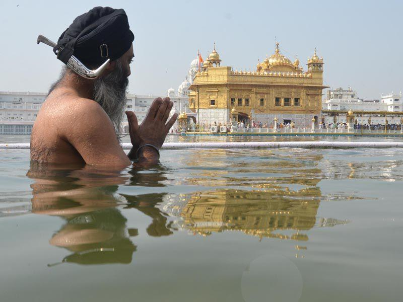 A devotee taking bath in the holy sarovar at the Golden Temple in Amritsar on Monday. (Sameer Sehgal/HT)