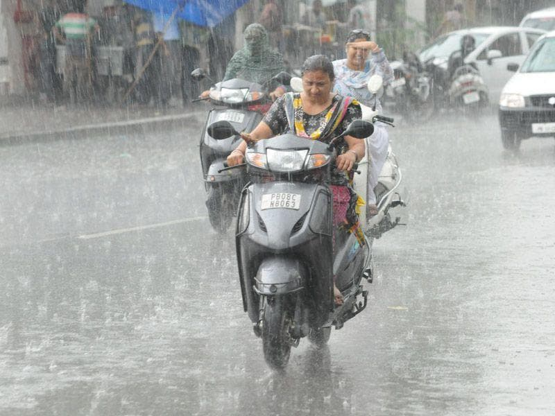 A lady driving scooter during rain in Jalandhar.Pardeep Pandit/HT