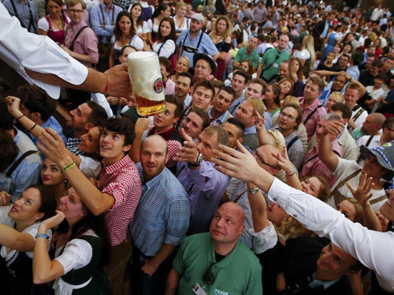 Visitors reach for a mug of beer from the first barrel during the opening ceremony for the 182nd Oktoberfest in Munich , Germany on Saturday. Millions of beer drinkers from around the world will come to the Bavarian capital over the next two weeks for Oktoberfest, which runs until October 4. (REUTERS)