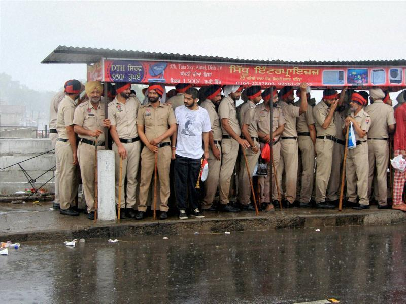 Policemen stand under a shelter during rainfall in Bathinda on Sunday. (PTI)