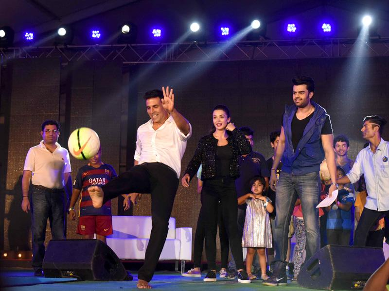 Akshay Kumar plays football as Amy Jackson and Manish Paul watch at the HT GIFA grand opening ceremony in Tau Devi Lal stadium, in Gurgaon, India, on Sunday, September 20, 2015.  (Vipin Kumar/Hindustan TimeS)