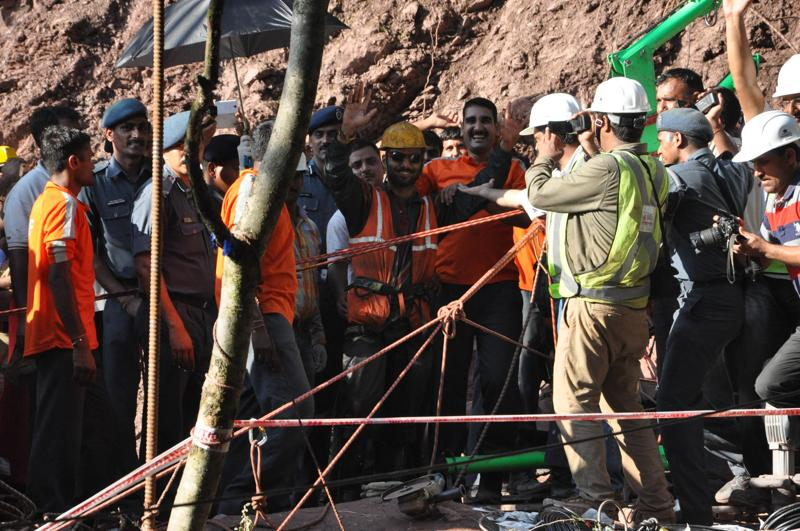 A rescued workers waves at the mediapersons as he comes out of the tunnel where he had been trapped for more than a week.  (HT Photo)