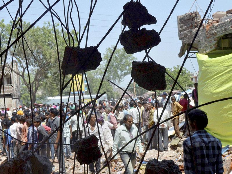 Onlookers gather at the site of Saturday's explosion in the town of Petlawad, Jhabua in central Madhya Pradesh. (PTI Photo)