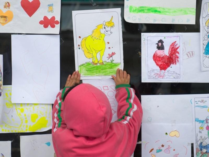 A migrant child looks at a unicorn drawing during the Muslim holiday of Eid al-Adha in a shelter at a former shopping mall in Graz, about 190 kms (118 miles) south of Vienna, Austria. (AP)