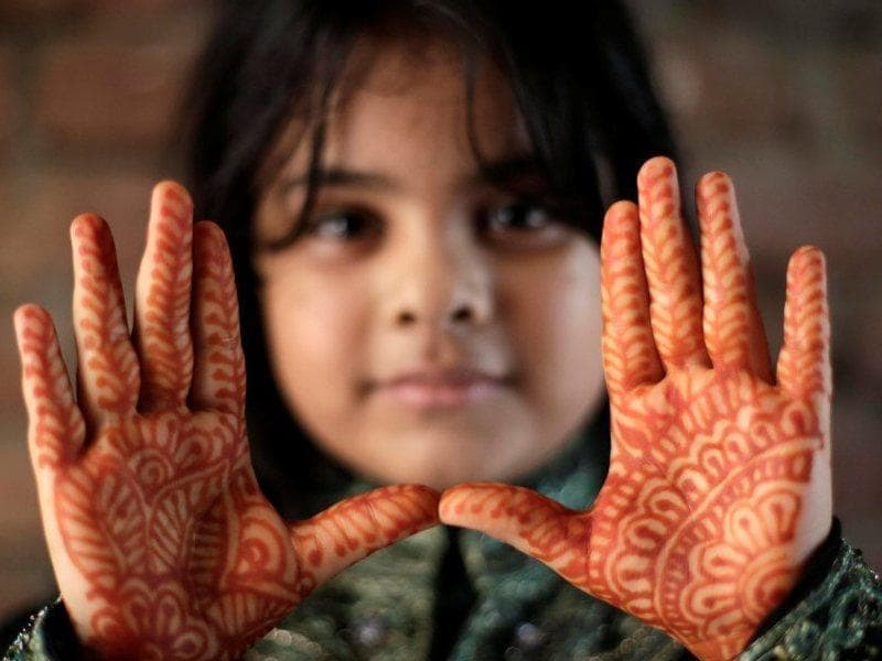 A Bangladeshi girl shows her decorated hands with hena painting, during the Eid al Adha festival in Dhaka, Bangladesh. (EPA)