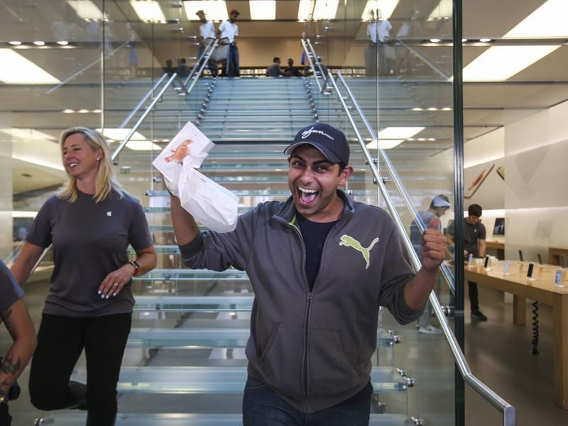 Bobby Evans, 28, of Beverly Hills and one of the first customers, walks out with his Apple iPhone 6S at the Apple store in Los Angeles. (AP Photo)