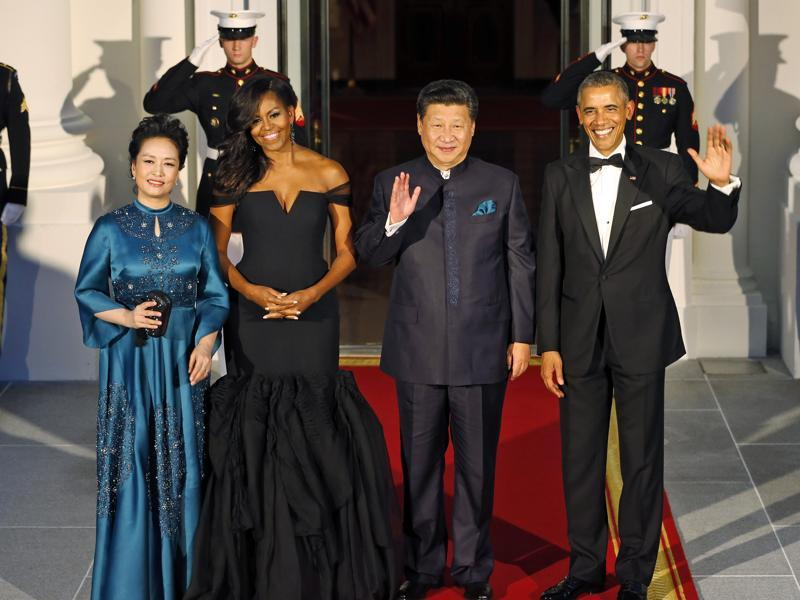 President Barack Obama, right, and Chinese President Xi Jinping, second from right, wave along with, wives Peng Liyuan, left, and first lady Michelle Obama as they arrive for a state dinner at the White House in Washington. (AP Photo)