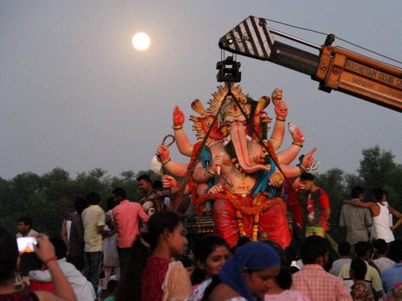 Devotees immerse an idol of Lord Ganesh during Ganesh Chaturthi celebrations at Akhnoor near Jammu on Sunday. (PTI Photo)