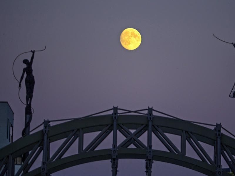 Statues are seen silhouetted against the moon in Brussels, Belgium September 26, 2015. On Saturday, a perigee moon coincided with a full moon creating a