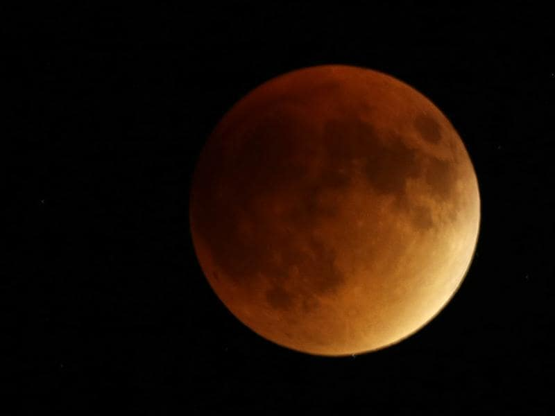 Earth's shadow obscures the view of a so-called supermoon during a total lunar eclipse Sunday, September 27, 2015, near Lecompton, Kan. It was the first time Sunday that the events have made a twin appearance since 1982, and they won't again until 2033.  (AP Photo)