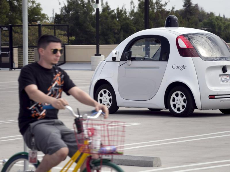 A Google employee on a bicycle acts as a real-life obstacle for a Google self-driving prototype car to react to (REUTERS)
