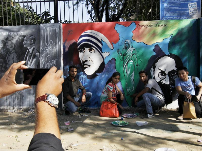 Students take their picture with Mahatma Gandhi's graffiti near Delhi University on his 146th birth anniversary in New Delhi.  (Ravi Choudhary/Ht photo)