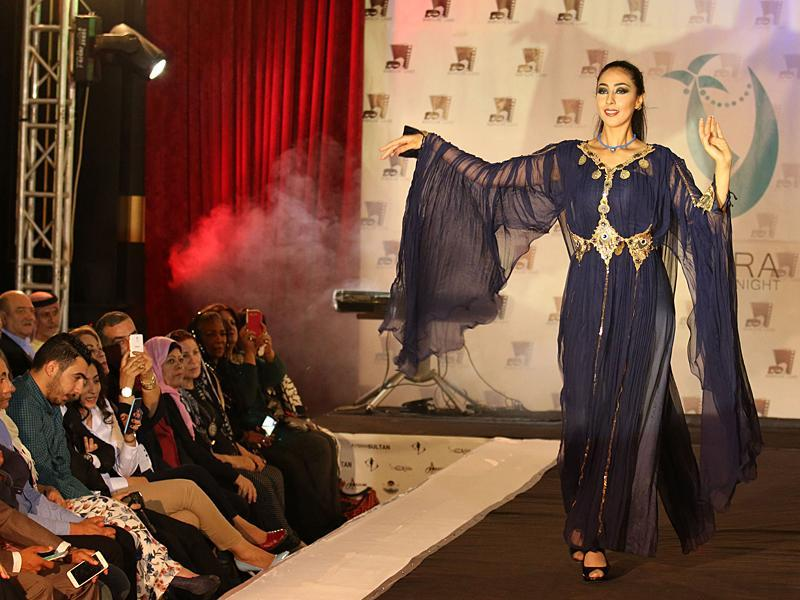 A model in an ink-blue flowing gown by a local designer during the Basra Fashion Night… (AFP)
