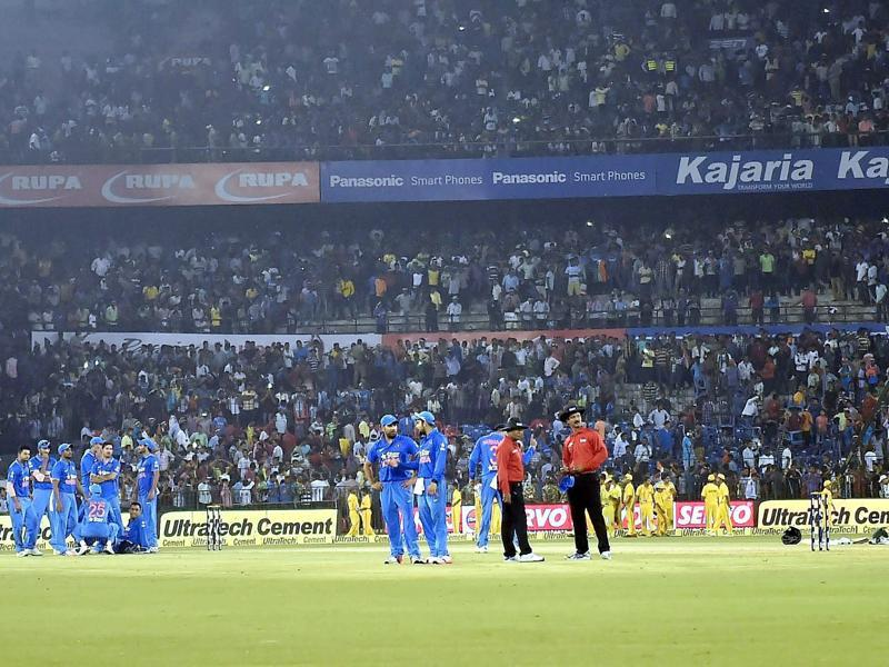 Indian and South African players, as well as match officials, wait  for play to resume. (PTI Photo)