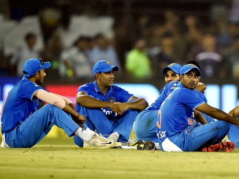 Indian cricketers sit near the pitch after play in the second innings was halted due to crowd disturbance.  (PTI Photo)