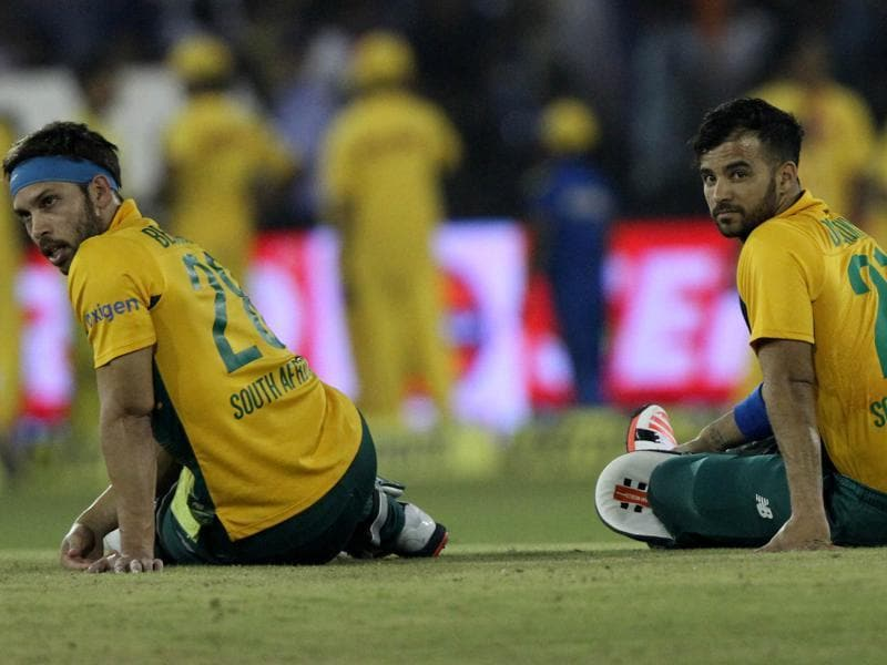 Farhaan Behardien, left, and Jean-Paul Duminy of South Africa wait for play to resume as an angry crowd threw bottles into the ground. (Subhendu Ghosh/HT Photo)