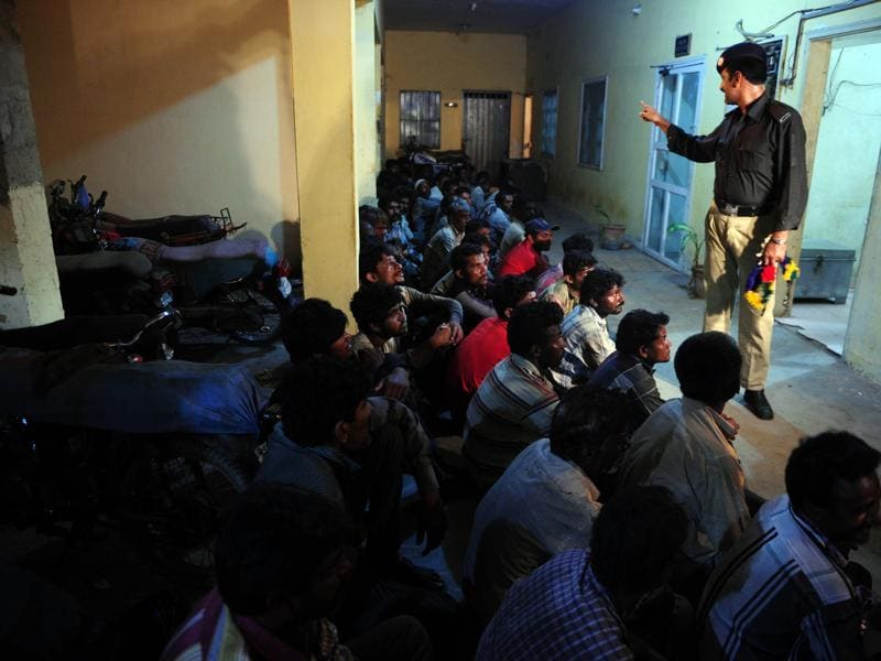A Pakistani policeman counts arrested Indian fishermen at a police station in Karachi. (AFP)