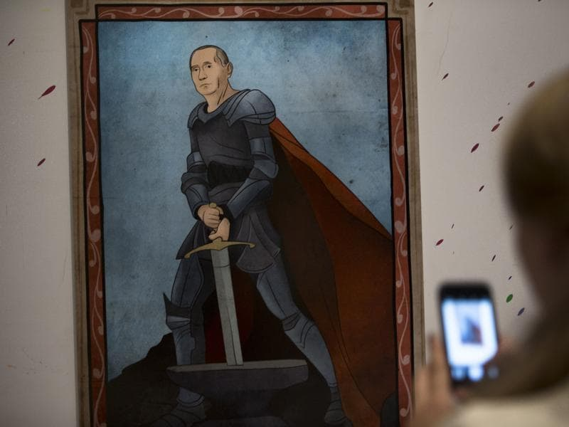 A woman takes a picture of an artwork depicting Russian President Vladimir Putin as King Arthur during the