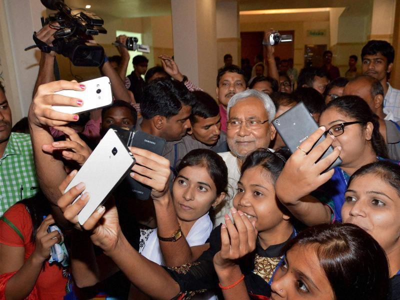 Bihar chief minister Nitish Kumar poses for a selfie with girls during a programme on Bihar elections in Patna. (PTI)