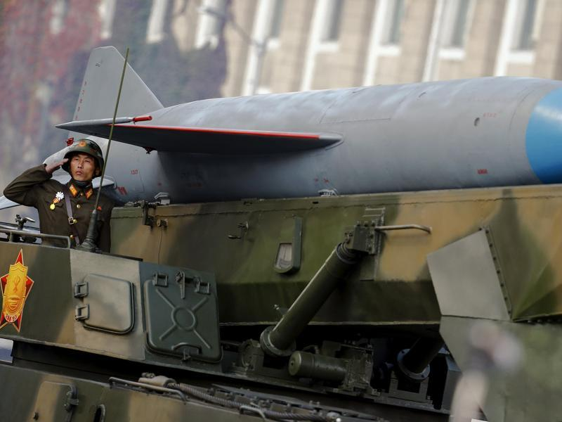 A soldier salutes from atop vehicle carrying a missile past a stand with North Korean leader Kim Jong Un. (REUTERS)