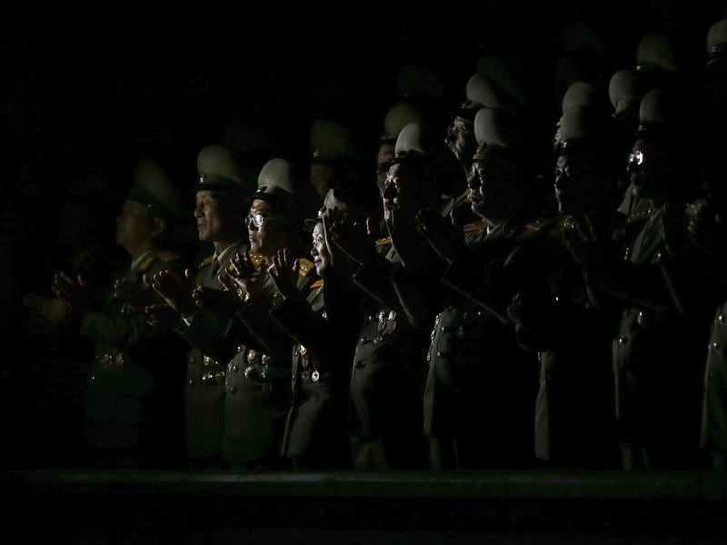 Senior North Korean military officers are lit by light from a camera as they follow the performance on Pyongyang's main Kim Il Sung Square. (REUTERS)
