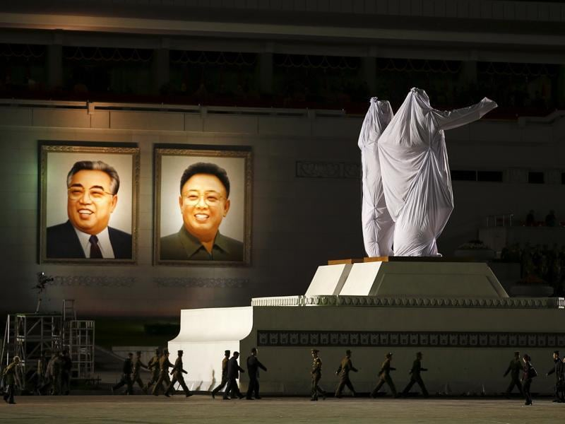 Large covered statues of North Korea's founder Kim Il-sung and former leader Kim Jong-il are wheeled past their portraits after the parade celebrating the 70th anniversary of the founding of the ruling Workers' Party of Korea. (REUTERS)