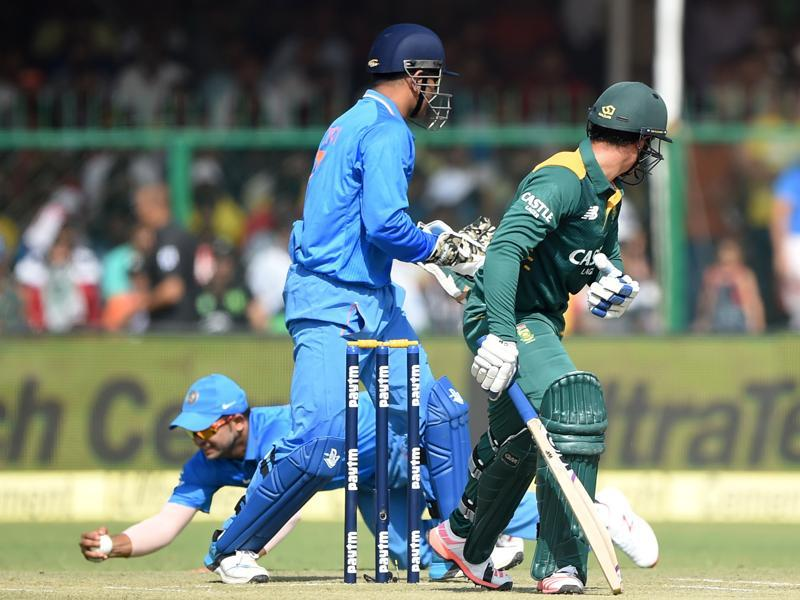 India's captain Mahendra Singh Dhoni, centre, and South Africa's Quinton de Kock, right, look back as India's Suresh Raina takes a catch to dismiss de Kock during the first innings. (AFP Photo)