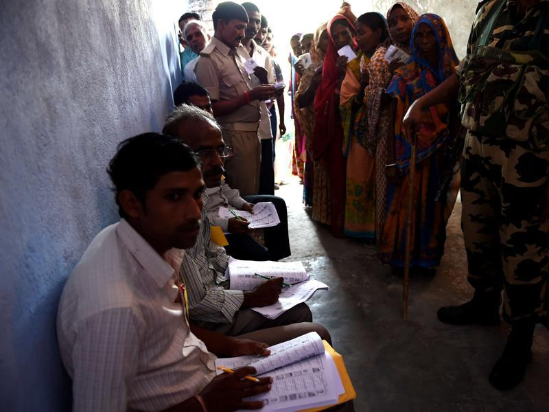 Election officials (L) sit at a voting centre as voters queue to cast their ballots in the village of Banbira in Samastipur district. (AFP)