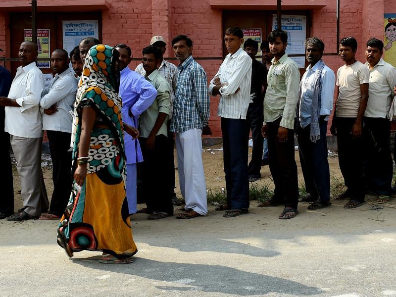 Voters queue to cast their ballots as a woman leaves after polling in the village of Banbira in Samastipur district on October 12, 2015. (AFP)